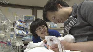 NICUで肌着を着る赤ちゃんと家族